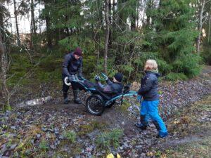 Jyrkempia esteitä ylittäessä maastopyörätuolin käsittelemiseen tarvitaan kaksi avustajaa